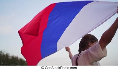 The symbol of Russia is a tricolor flag: white, blue and red. A young woman holds a flag behind her back in the wind.