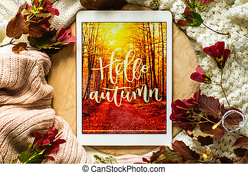 The tablet says the word hello Autumn with red leaves and a dais on the wooden background. Concept of the autumn. View from above.