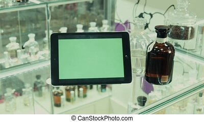 The tablet with the green screen on a show-window in shop of perfume