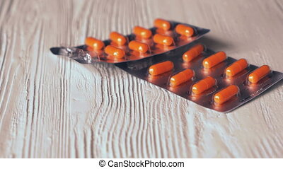 The tablets in orange capsules fall on white table