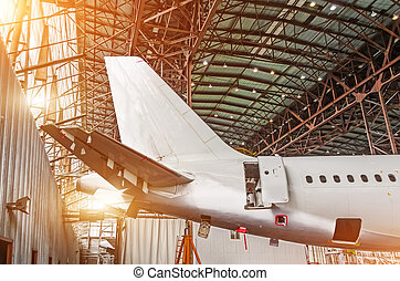 The tail of the aircraft in the hangar, maintenance of the plane.