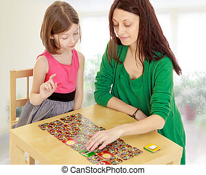 The teacher and the girl at the table studying the cards -...