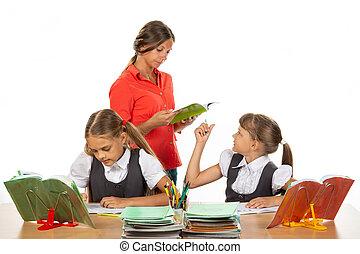 The teacher helps the schoolgirl to understand the task