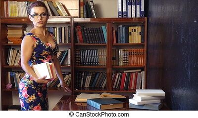 the teacher reads a book in the library of the University 1