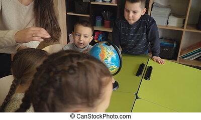 the teacher teaches children using the globe - teacher...