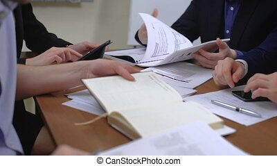 The team of young businesspeople. They work together with the documents and figures. In the office.