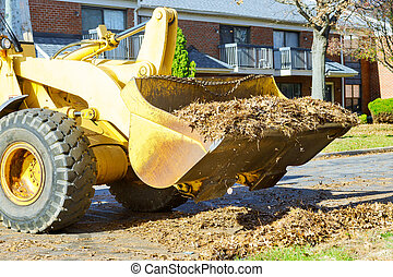 The teamwork on city improvement cleaning autumn leaves in the fallen leaves with a tractor