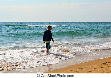 The teenage boy goes on the seashore.