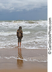 The teenager costs on the seashore in a jacket and barefoot.