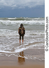 The teenager costs on the seashore in rainy weather a back in a shot