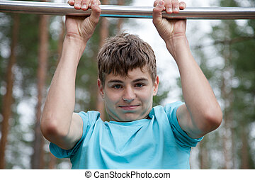 The teenager doing exercise on a horizontal bar