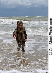 The teenager goes on the seashore in a jacket and barefoot.