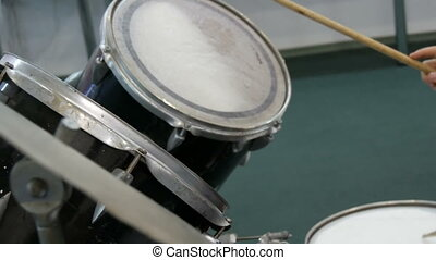The teenager is learning to play drum set. Drum sticks knock...