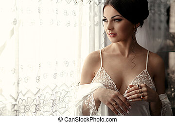 The tenderness bride stands near window