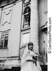The tenderness bride with bouquet stands near castle