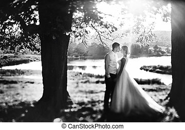 The tenderness brides stand near lake