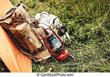 the tent and two backpacks near a tourist track in mountains on green grass