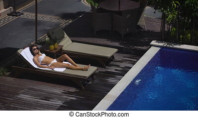 The territory of the hotel. The girl in a white bathing suit lying on a lounger by the pool. It relaxes and gets pleasure from their holidays. Weather in Bali does not fail, because the sun is shining