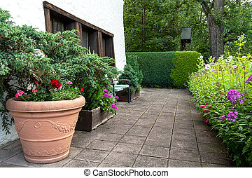 The territory of the house is decorated with a huge ceramic pot with flowers and coniferous trees.