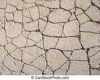 The texture of old asphalt with cracks.
