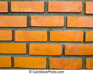 The texture of orange brick wall. They are arranged in rows, alternating beautifully. Around each brick is surrounded by gray cement