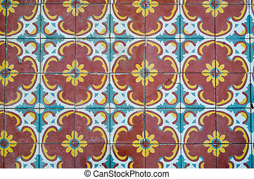 The texture of square ceramic tiles with patterns from traditional Arabic ornaments and flowers of yellow and blue. The background
