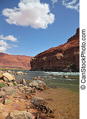 The rapid course of the Colorado River in the red rocks of the desert