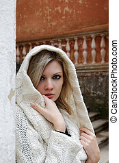 The thoughtful girl in knitted dress on a background of the old walls