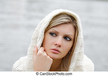 The thoughtful girl in knitted dress on a background of water