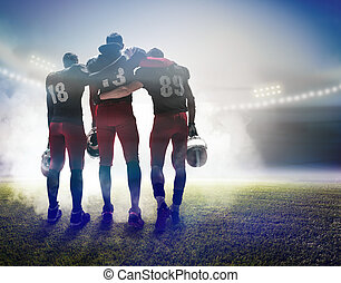 The three american football players on on stadium background