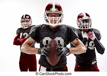 The three american football players posing with ball on white background