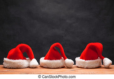 The three Santa red hats on wooden background