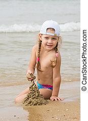 The three-year girl builds a sand castle on the beach