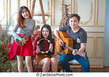 The Three young Boy&girl friends having fun and smiling and Playing Guitar and instruments.