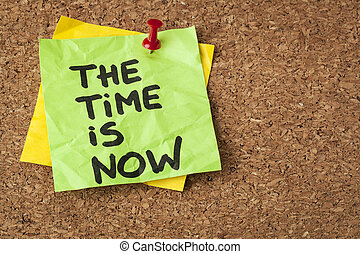 the time is now - motivational reminder on a green sticky ...