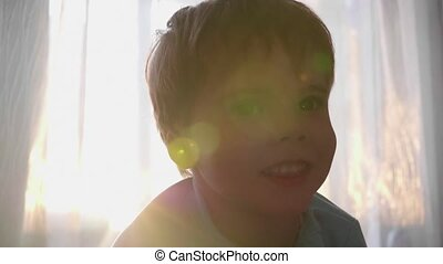 The time of sunset. A small child looks at the camera near the window and smiles. Face close-up. The sun's rays through the window
