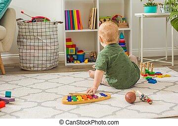 The toddler boy chooses toys in the playroom