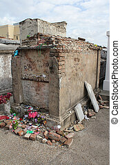 The tomb of unknown Voodoo practitioner, St. Louis Cemetery #1, New Orleans, Louisiana with a Voodoo doll in the upper left corner and tributes along the base.