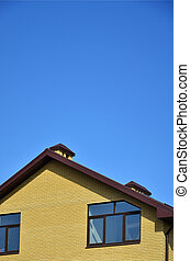 The top of a residential building of yellow brick