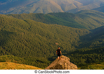 The top of Mount Pip Ivan, a tourist admires the scenery from the top, a hike in the Ukrainian Carpathians, fascinating epic photos.