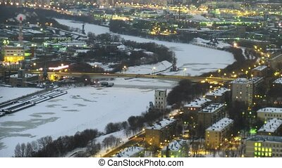 The top view on a winter city, on centre the frozen river. Gradually darkens. Time lapse.