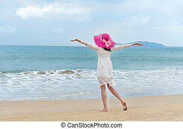 tourist in bright hat and white dress on the beach