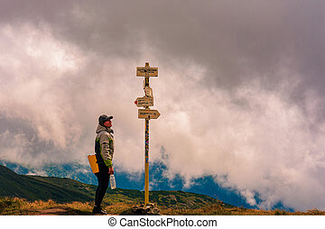 The tourist studies the indicator in the mountains, the direction to move further, the Montenegrin ridge of the Carpathian mountains.