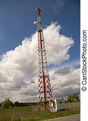 The tower of a mobile operator against the blue sky with white clouds
