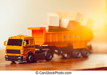 The toy car and building truck on wooden table
