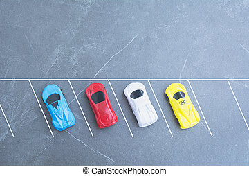 The toy cars parking in car park on background with copy space.