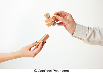 The toy wooden puzzle in hands isolated on white background