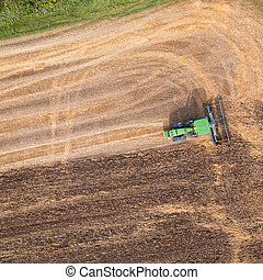 The tractor plows the field, preparing the soil for agricultural work. Top view.