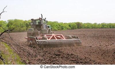 The tractor plows the soil. - The tractor plows the soil...