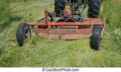 The tractor pulls the grass mowing unit.